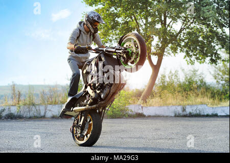 Ivano-Frankivsk, Ukraine - 28 August 2015 : Young biker wearing protective helmet is maiking tricks on summer cite street. Green trees and plants,blue sky on background. - Stock Photo