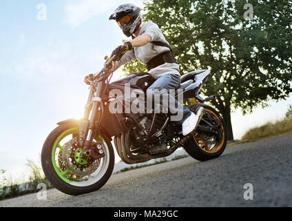 Ivano-Frankivsk, Ukraine - 28 August 2015 : Photo of biker is posing sitting on his colorful sport motorcycle on summer street, filled with shine of sunset. Man wearing protective helmet for bikers. - Stock Photo