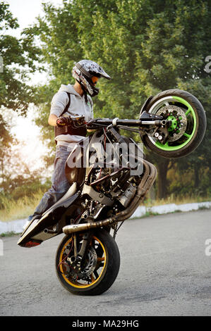 Ivano-Frankivsk, Ukraine - 28 August 2015 : Good photo of a stuntman doing trick riding motorcycle on one cycle along the street. Green tricks on background. Summer sunset. - Stock Photo