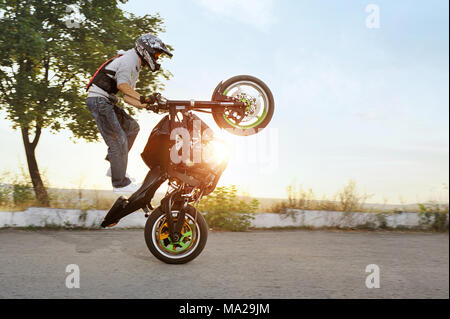 Ivano-Frankivsk, Ukraine - 28 August 2015 : colorful sideview of extreme impressing stunt driver is jumping on his sport motorcycle while riding in extreme way. Summer sunny evening. - Stock Photo