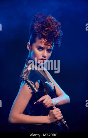 Side view of fantastic girl keeping sharp metallic axe with thorns. Female warrior standing on dark blue smoky background. Model wearing black top with opened shoulders, make up and stylish hairdress. Stock Photo