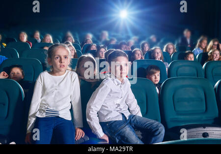 Frontview of boy and girl sitting in the cinema hall by watching new movie or cartoon. Boy is looking at camera, girl is watching film on the cinema screen. exited, emotional children on background. - Stock Photo