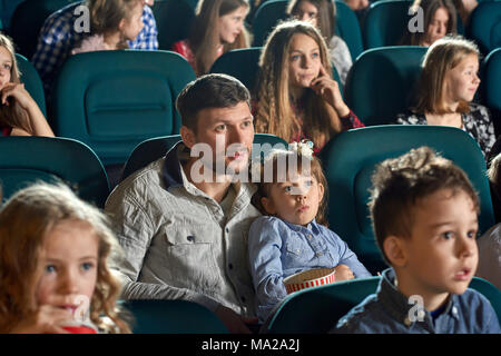 Photo of father with little daughter watching movie in the cinema. Girl is looking very cute and interested, eating popcorn. There are other exited people on background. - Stock Photo