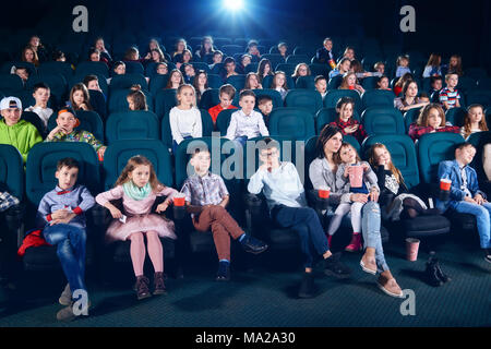 Frontview of people sitting in the cinema hall. Boys and girls watching interesting movie and looking very emotional, frightened and exited. Children wear colorful trendy clothes. - Stock Photo