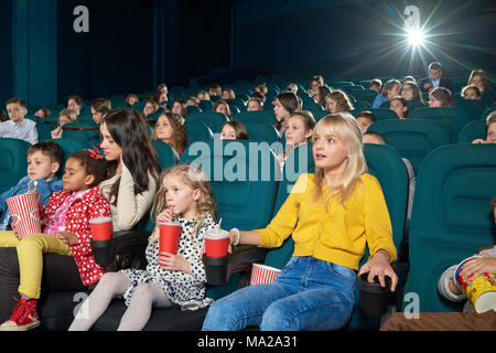 Interested girls watching new movie in the cinema. Children drinking fizzy drinks and eating popcorn. Looking emotional, exited, happy and satisfied. Other people on background. - Stock Photo