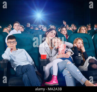 Pretty senior sister is watching movie or cartoon in the new cinema hall with junior children . children looking very interested and exited. There are other people on the backgroung. - Stock Photo