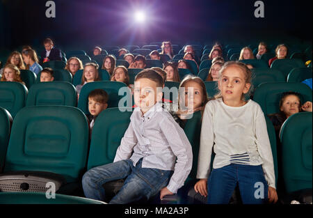 Little boy and girl sitting in the cinema hall by watching new movie or cartoon. Boy is looking at camera, girl is watching film on the cinema screen. Other exited, emotional children on background. - Stock Photo