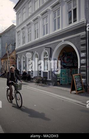 Man cycling in front of facade of Restaurant, Aarhus, Denmark - Stock Photo