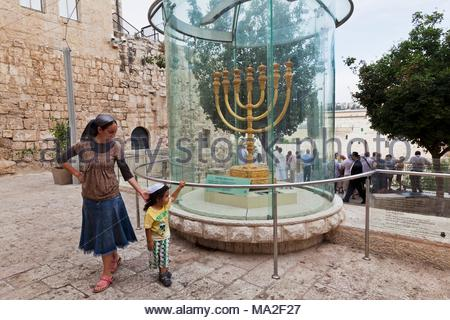 A mother and child standing in front of the Golden Menorah in the old town of Jerusalem - Stock Photo