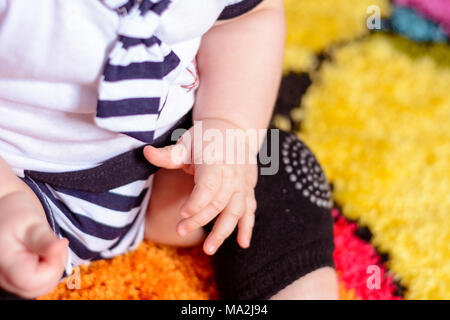 A pretty baby in a striped shirt and hats seated on the mat in the room 2018 - Stock Photo