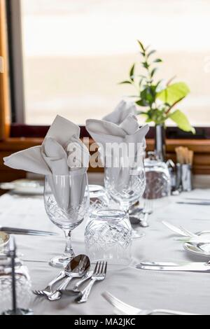An elegantly laid table in the dining car of the luxury train Rovos Rail (journey from Durban to Pretoria, South Africa) - Stock Photo