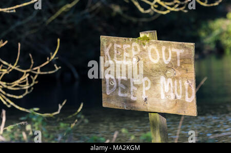 Keep out deep mud danger warning sign in a muddy lake in the UK. - Stock Photo