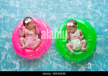 Two week old twin baby sisters sleeping on tiny, inflatable, pink and green swim rings. They are wearing crocheted swimsuits. - Stock Photo