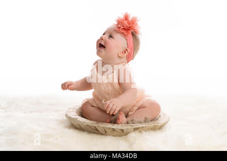 A smiling, seven month old baby girl wearing a peach colored, knitted romper. She is sitting in a wooden bowl. Shot in the studio on a sheepkin rug. - Stock Photo