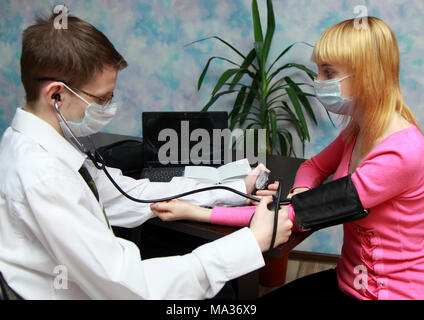 The doctor in a white robe measures the patient's blood pressure - Stock Photo