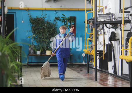 Old woman cleaner in workwear on manufacturing site - Stock Photo