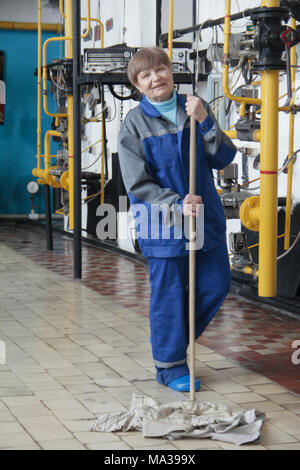 Smiling old woman cleaner in workwear on manufacturing site - Stock Photo