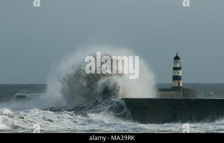 Huge waves hit pier and lighthouse at Seaham - Stock Photo