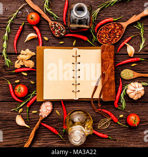 Top view open recipe book with chili peppers, garlic, oil, balsamic vinegar, salt, herbs and spices on wooden background. Cooking concept. Selective f - Stock Photo