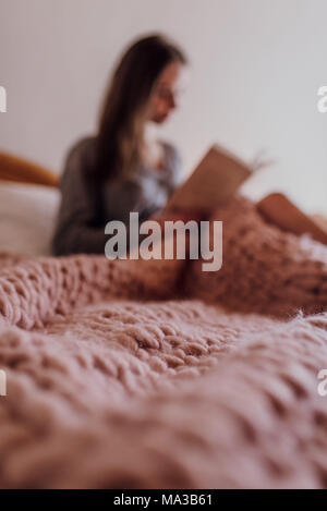 young woman sitting in bed and reading a book