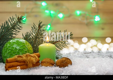 Christmas decoration, candle, nuts, cinnamon sticks in front of fir tree in the snow - Stock Photo