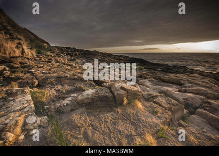 Sunset on rocky beach in Moelfre.Stunning landscape of Anglesey island coastline,North Wales,Uk.Dark,dramatic cloudy sky over british coast.Nature uk. - Stock Photo