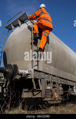 A railway maintenance worker wearing hi viz clothing climbing a ladder onto a rail tanker to inspect the upper deck whilst working at height. - Stock Photo