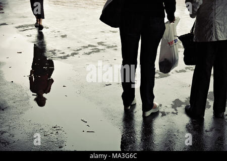Reflection of a woman in a puddle afer rain, Helsinki, Finland - Stock Photo