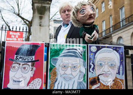 London, UK. 29th March, 2018. Boris Johnson lookalike Drew Galdron stands with a puppet of Prime Minister Theresa May during a protest opposite Downing Street by pro-EU activists to mark the first anniversary of the triggering of Article 50 and a year before the UK's exit from the European Union, or Brexit, is scheduled to take place. Protesters dressed as 'EU super heroes' and 'Brexit villains'. Credit: Mark Kerrison/Alamy Live News - Stock Photo