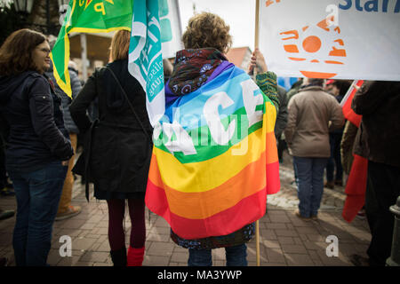 30 March 2018, Germany, Bruchkoebel: A protestor wrapped in a peace flag attends an Easter rally. Over Easter, several peace marches are planned in the Hesse region. Topics include demilitarization, German miliary operations in the Middle East, stopping weapons exports and phasing out of nuclear energy. Photo: Frank Rumpenhorst/dpa - Stock Photo