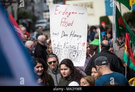 30 March 2018, Germany, Bruchkoebel: 'Erdogan und Assad nach Den Haag in den Knast' (lit. 'Get Erdogan and Assad to The Hague and to jail') reads the demand written on the sign of a protestor at an Easter rally. Over Easter, several peace marches are planned in the Hesse region. Topics include demilitarization, German miliary operations in the Middle East, stopping weapons exports and phasing out of nuclear energy. Photo: Frank Rumpenhorst/dpa - Stock Photo