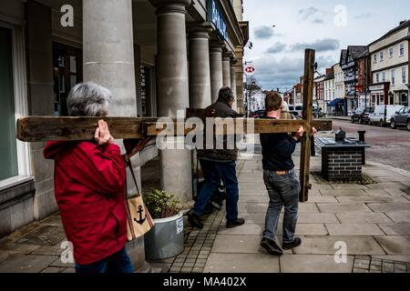 LEOMINSTER, HEREFORDSHIRE, UK - MARCH 30: Members of Leominster Baptist Church arrive with the cross outside Barclays Bank on the High Street as the Christian community in Leominster gather to take part in a Good Friday procession as part of Holy Week on March 30, 2018. During the Walk of Witness they carry the symbolic cross from the Baptist Church on Etnam Street through the medieval market town square to the Priory Church on Church Street where the cross will be erected. Many towns and villages already hold walks or marches of witness as a sign of their common belief in the death and resurr - Stock Photo