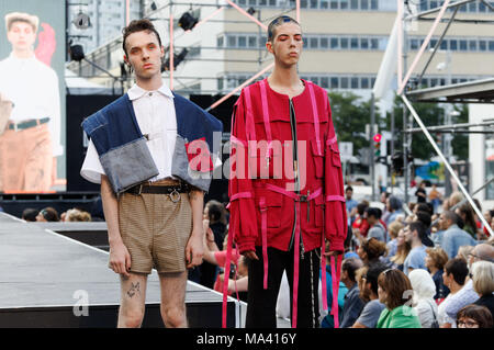 Montreal,Canada. Two male models pose on the runway at the  Nancy VTMT  fashion show, featuring Quebec City designers held during the Fashion and Desi - Stock Photo