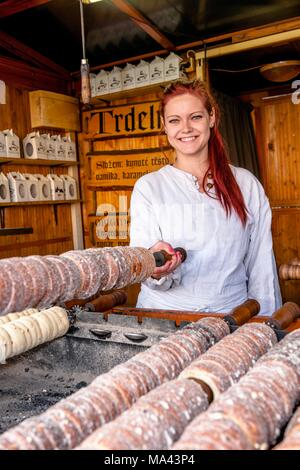 A woman selling 'trdelniks', a traditional cake, on the central marketplace in Prag, Czech Republic - Stock Photo