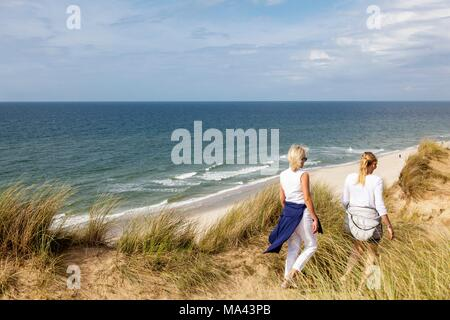 Walkers exploring the dunes on the Rotes Kliff (Red Cliff) on the island of Sylt, Germany - Stock Photo