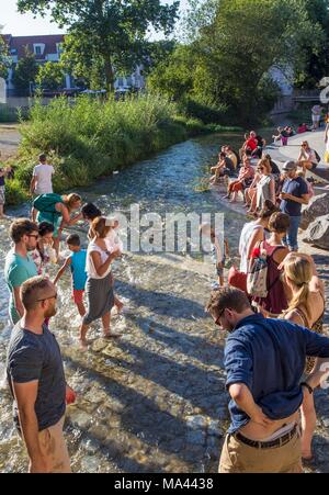 People cooling off in the Gera river on the Krämer bridge in Erfurt, Thuringia, Germany - Stock Photo
