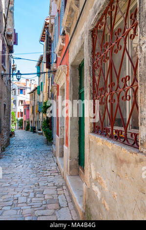 Cozy Old Town paving stone street with medieval buildings facades in Rovinj Istria Croatia - Stock Photo