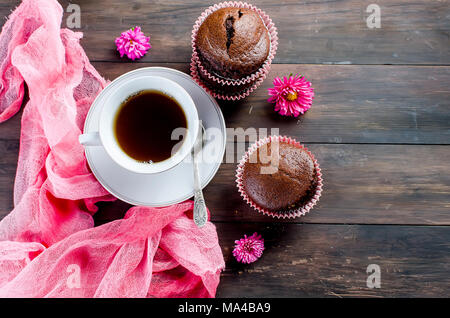 chocolate muffins and a cup of coffee breakfast  still life on a dark wooden table. Copy space, top view. - Stock Photo