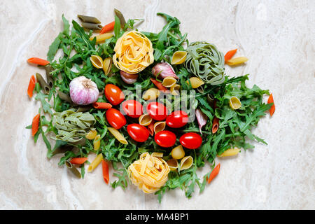 Rocket Arugula with plum tomatoes and garlic with Tagliatelle and penne pasta tricolore ingredients for Italian food on marble table - Stock Photo