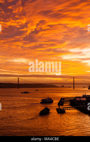 Sunset over the Tagus River off the Lisbon waterfront in Portugal.  In the background can be seen the Ponte 25 de Abril. - Stock Photo