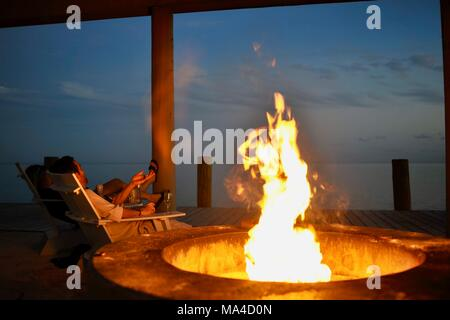 Flickering flames in outdoor fire pit along pier in Florida Keys, USA - Stock Photo