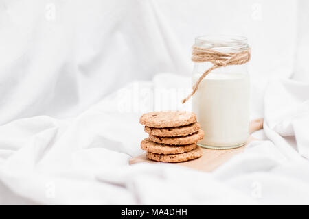 Photo of a jar of milk and cookies on a wooden board on a bed sheet - Stock Photo