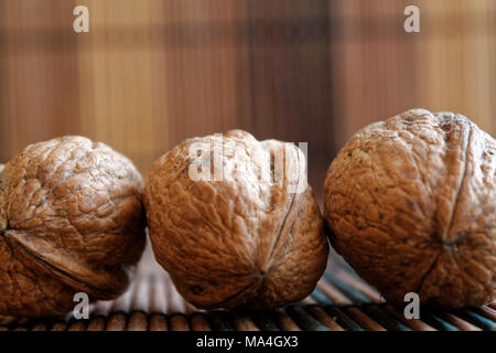 Three walnuts lie on a wooden bamboo table, background for web site or mobile devices. - Stock Photo