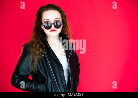 A moody attrractive young 13 thirteen year old teenage adolescent girl wearing a black leather jacket, on a red background, in a  photo studio , UK - Stock Photo