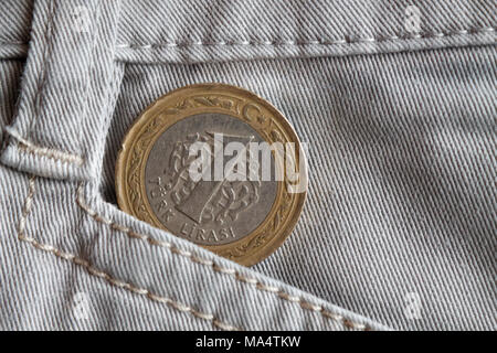 Turkish coin with a denomination of one lira in the old pocket of beige denim jeans - Stock Photo