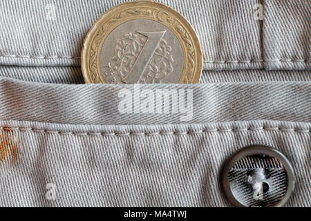 Turkish coin with a denomination of one lira in the pocket of beige denim jeans with button - Stock Photo