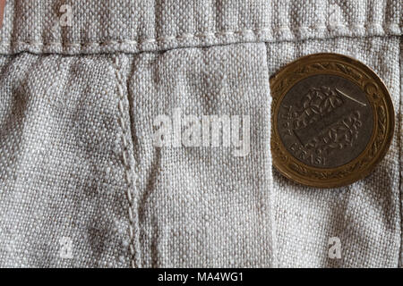 Turkish coin with a denomination of one lira in the pocket of old linen pants - Stock Photo