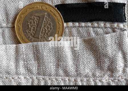 Turkish coin with a denomination of one lira in the pocket of old linen pants empty black stripe for label - Stock Photo