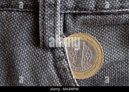 Turkish coin with a denomination of one lira in the pocket of old brown denim jeans - Stock Photo