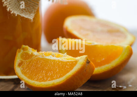Orange homemade jam  and sliced oranges on the wooden table - Stock Photo